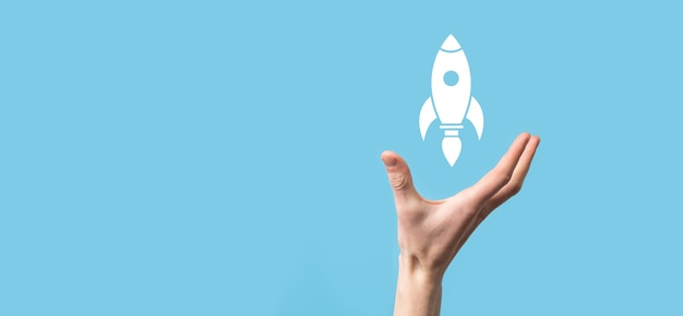 Mannenhand met raket pictogram dat opstijgt, lancering op blauwe achtergrond. raket lanceert en vliegt uit, opstarten van bedrijven, pictogrammarketing op moderne virtuele interface. opstarten concept.