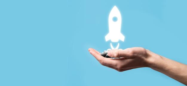 Mannenhand met raketpictogram dat opstijgt, lancering op blauwe achtergrond. raket lanceert en vliegt uit, opstarten van bedrijven, pictogrammarketing op moderne virtuele interface. opstartconcept.