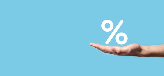 Mannenhand met rente percentage pictogram op blauwe achtergrond. rentetarieven financiële en hypotheekrentetarieven concept.