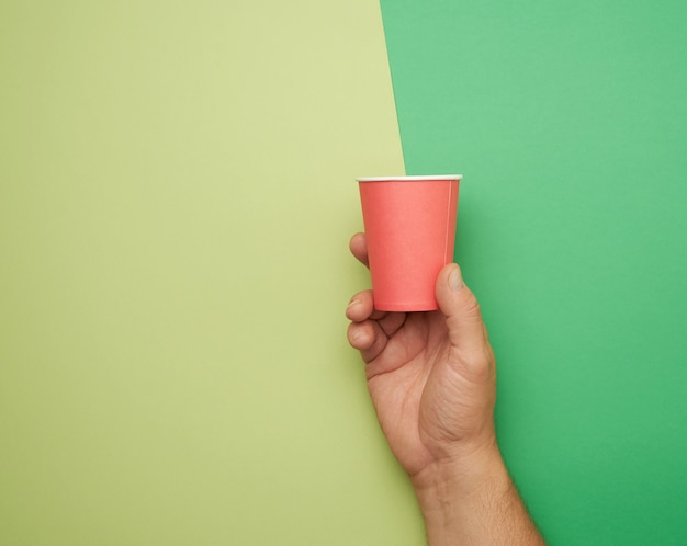 Mannenhand met rode papieren wegwerp beker, milieuvriendelijk concept, nul afval