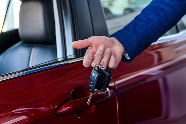 Mannenhand met sleutels tegen nieuwe rode auto