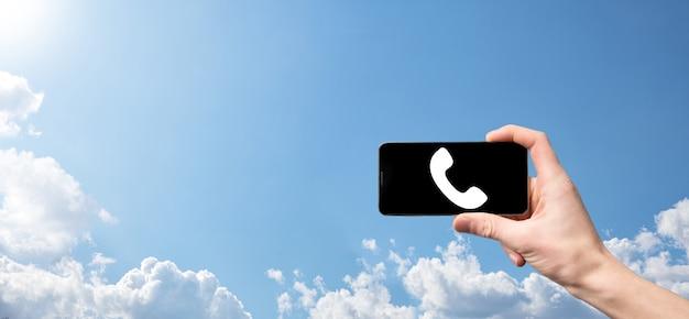 Mannenhand met slimme mobiele telefoon met telefoonpictogram. bel nu business communication support center customer service technology concept.