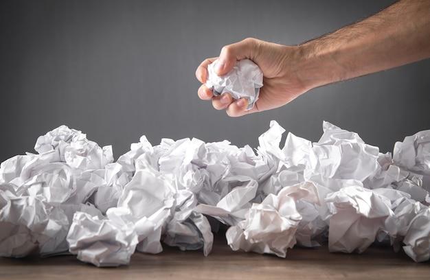 Mannenhand met verfrommelde papieren bal.