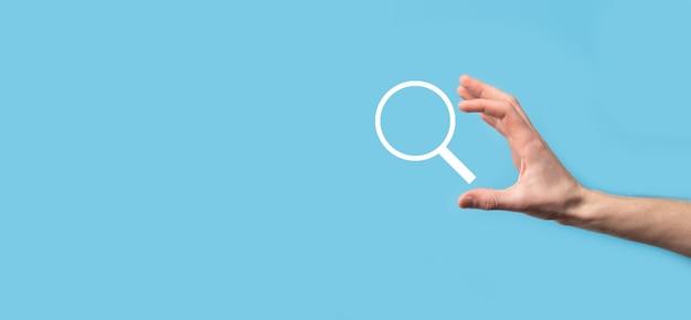 Mannenhand met vergrootglas, zoekpictogram op blauwe achtergrond. concept zoekmachineoptimalisatie, klantenondersteuning. surfen op internetgegevensinformatie. netwerkconcept.
