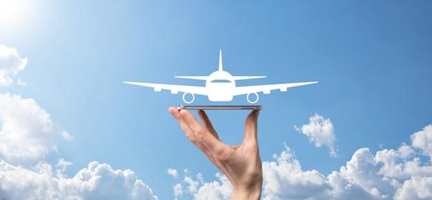 Mannenhand met vliegtuig vliegtuigpictogram op blauwe achtergrond. banner.nline ticketaankoop. reispictogrammen over reisplanning, transport, hotel, vlucht en paspoort. concept van het boeken van vliegtickets.