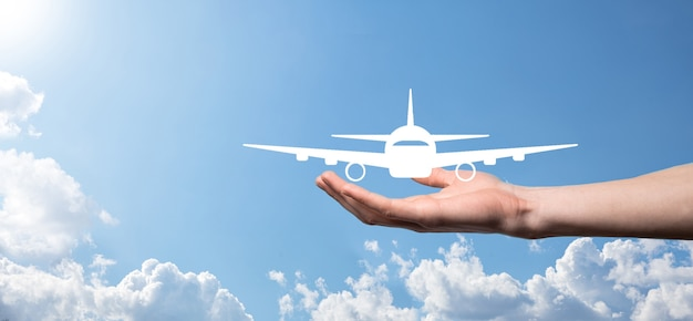 Mannenhand met vliegtuig vliegtuigpictogram op blauwe ondergrond