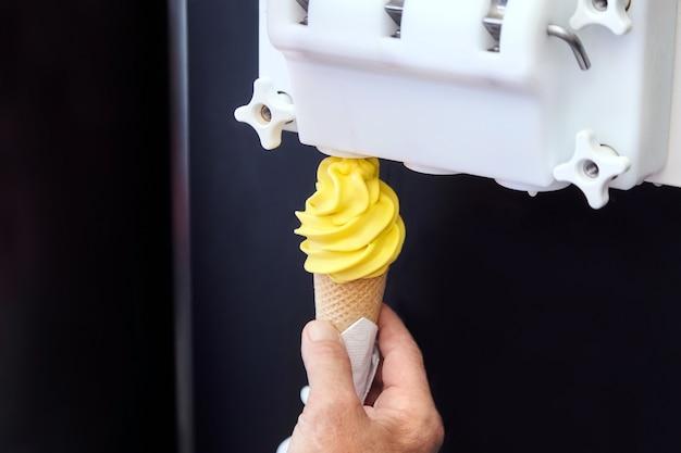 Mannenhand met wafelkegel met gele citroen gedraaide ijs uit de machine