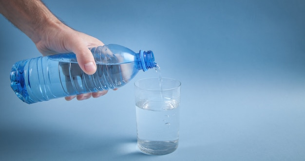 Mannenhand met waterfles gieten van water in glas.