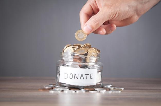 Mannenhand munt aanbrengend donatie pot.