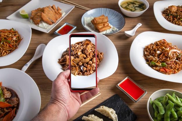 Mannenhand neemt een foto met smartphone van het eten op tafel in het oosterse restaurant.