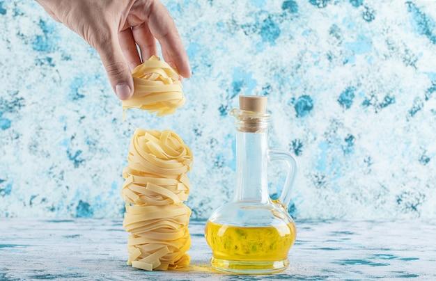 Mannenhand nemen pasta nest van blauw.