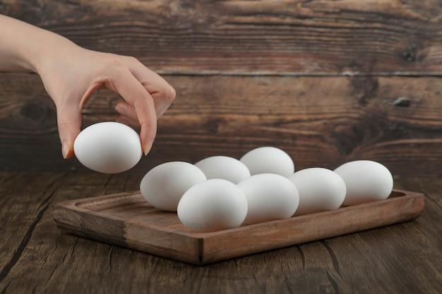 Mannenhand nemen rauw biologisch ei uit een houten bord.