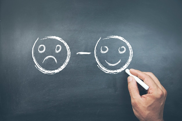 Mannenhand ongelukkig en gelukkig smileys gezichten puttend uit schoolbord