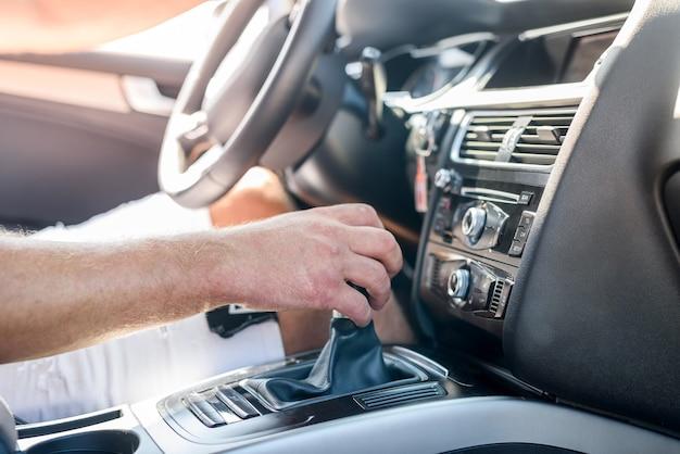 Mannenhand op transmissie versnelling in auto. dichte weergave van mannenhand met auto-interieur