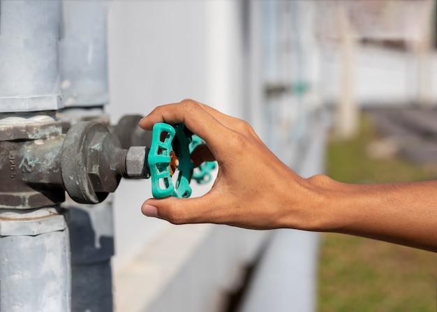 Mannenhand opent de tuinwaterkraan, giet schoon zoetwaterkraan, draai de kraan open, hands-off water, .