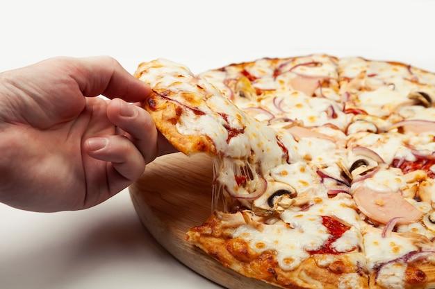 Mannenhand pakt een heerlijk stuk pizza met margarita of margarita met mozzarella