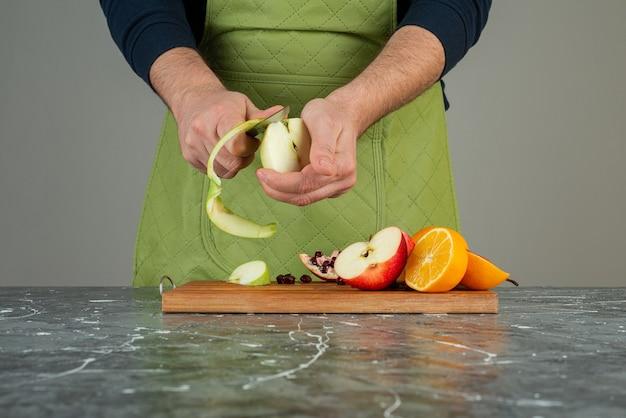 Mannenhand peeling groene appel bovenop een houten bord op tafel.