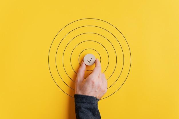 Mannenhand plaatsen van een houten gesneden cirkel met vinkje erop in het midden van getekende cirkels op gele achtergrond.