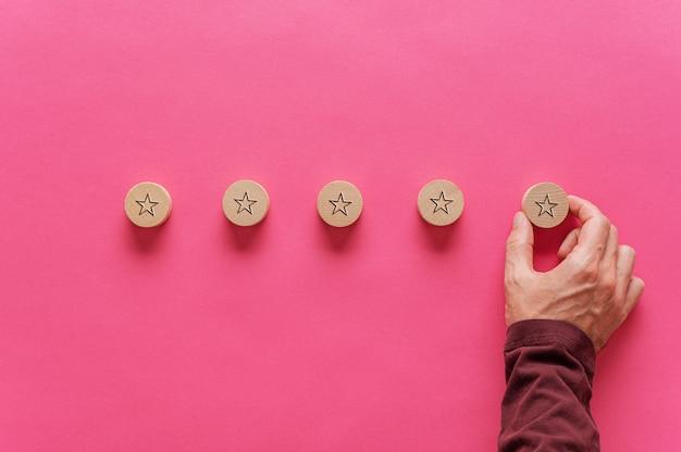 Mannenhand plaatsen van vijf houten gesneden cirkels met stervorm op hen in een rij