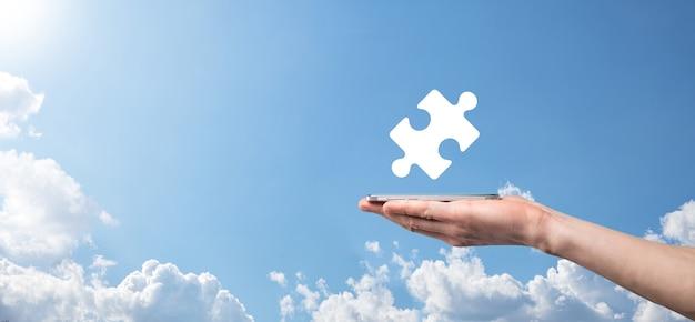 Mannenhand puzzel pictogram op blauwe achtergrond te houden. stukken die de fusie van twee bedrijven of joint venture, partnerschap, fusies en overnameconcept vertegenwoordigen.