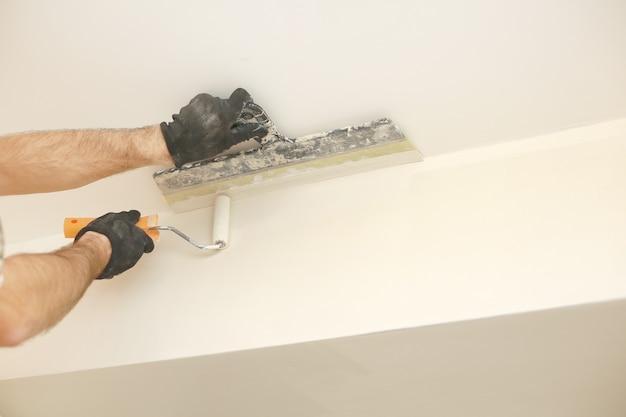 Mannenhand schilderij muur met verfroller. appartement schilderen, renoveren met witte kleur verf. kamerrenovatie in huis.