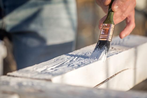 Mannenhand schildert met witte verf op hout, schilderij concept, close-up, plaats voor tekst