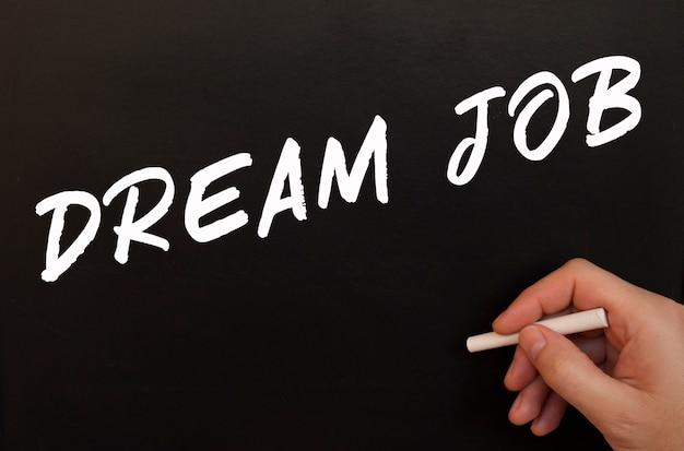 Mannenhand schrijft in krijt de woorden dream job op een zwart bord.