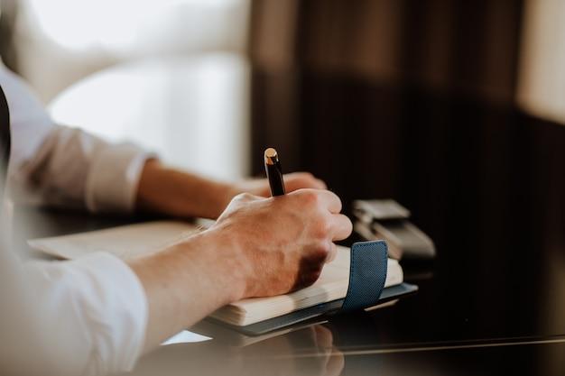 Mannenhand schrijven in notitie geplaatst op donkere glazen tafel. bedrijfsconcept. de nadruk ligt bij de hand. ruimte kopiëren.
