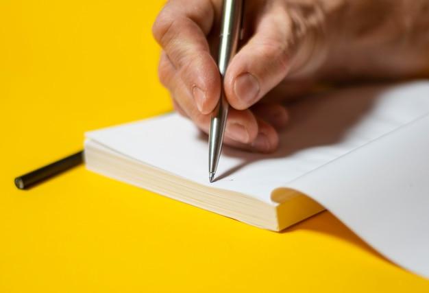 Mannenhand schrijven in notitieblok met pen