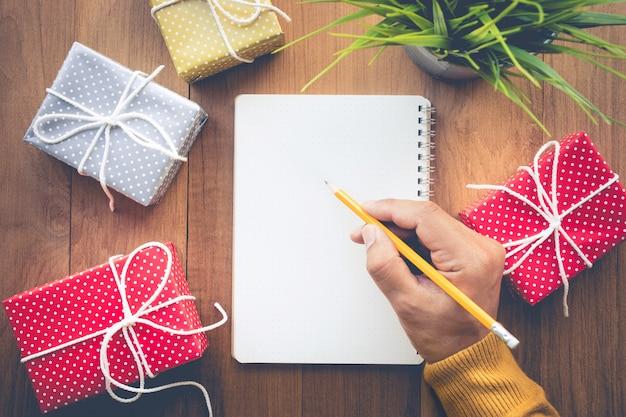 Mannenhand schrijven notitie papier met leuke geschenkdoos presenteert op werktafel achtergrond