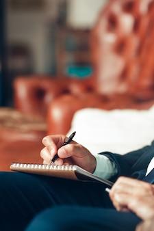 Mannenhand schrijven plannen in een kladblok.