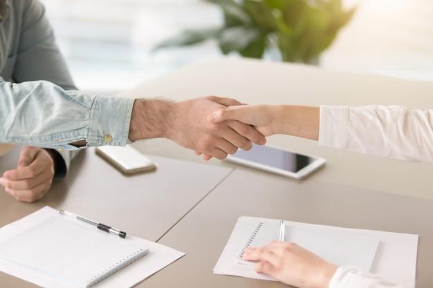 Mannenhand schudden hand van jonge vrouw over bureau