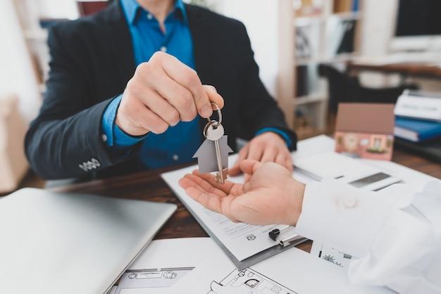 Mannenhand sleutels ontvangen met huis vorm trinket.