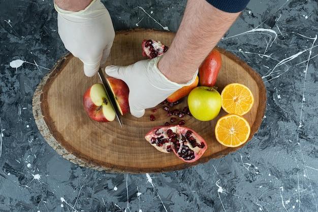 Mannenhand snijden rode appel bovenop een houten bord op tafel.
