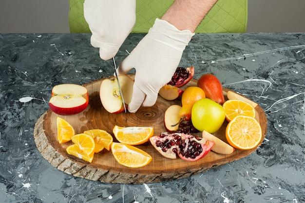 Mannenhand snijden verse rode appels op marmeren tafel.
