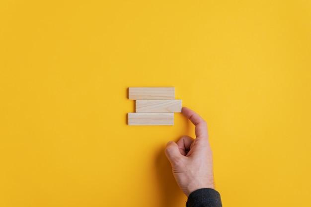 Mannenhand stapelen drie houten pinnen in een conceptueel beeld