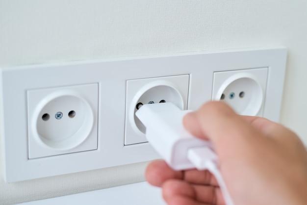 Mannenhand steekt witte stekker in het stopcontact
