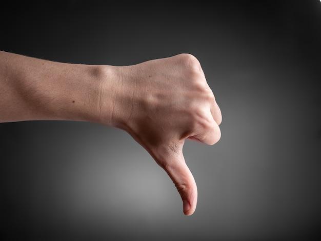 Mannenhand toont duim op grijze muur.