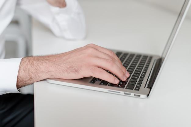 Mannenhand typen op laptop toetsenbord