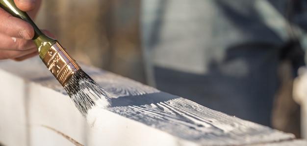 Mannenhand verven met witte verf op hout