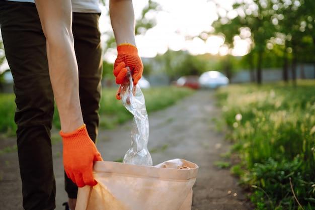 Mannenhand verzamelt plastic afval voor schoonmaak in het park. vrijwilliger met beschermende handschoenen verzamelt plastic fles.