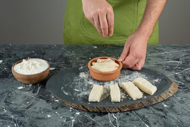 Mannenhand zout toe te voegen aan deeg op marmeren tafel.