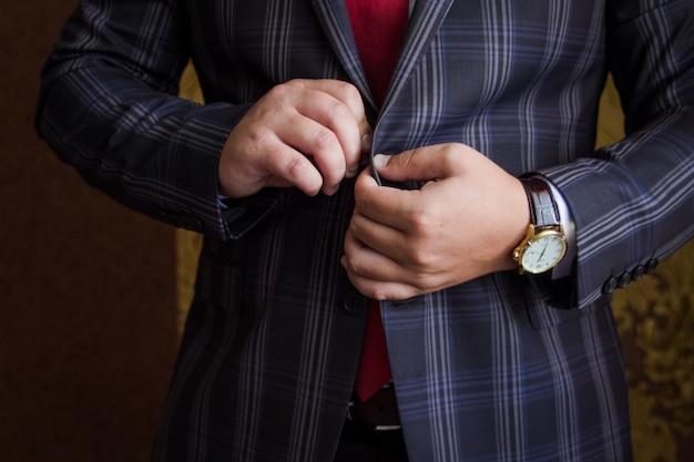 Mannenhanden bevestigen een knoop op een pak met strepen