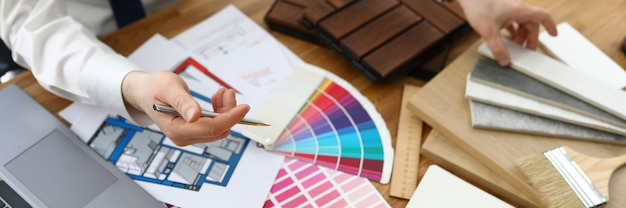 Mannenhanden boven tafel waarop monsters van afwerkingsmaterialen en kleurenschema's zich bevinden.