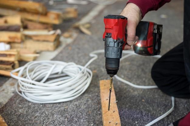 Mannenhanden gebruiken schroevendraaier tijdens bouwwerkzaamheden met hout binnenshuis.