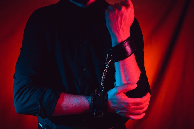 Mannenhanden geketend in lederen handboeien voor bdsm-seks. onderwerping en overheersing