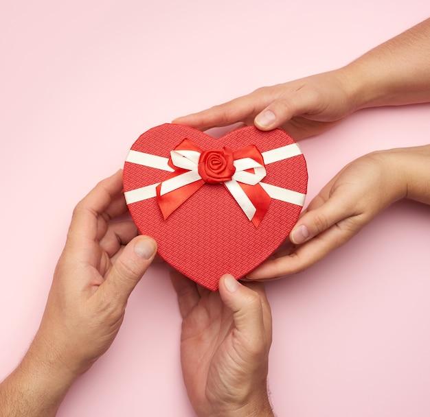 Mannenhanden geven een rode doos met een geschenk aan een vrouw, bovenaanzicht