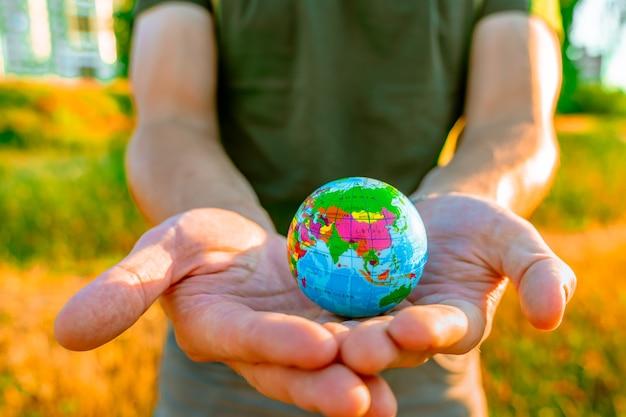 Mannenhanden houden een wereldbol vast bij zonsondergang in het park het concept van milieubescherming