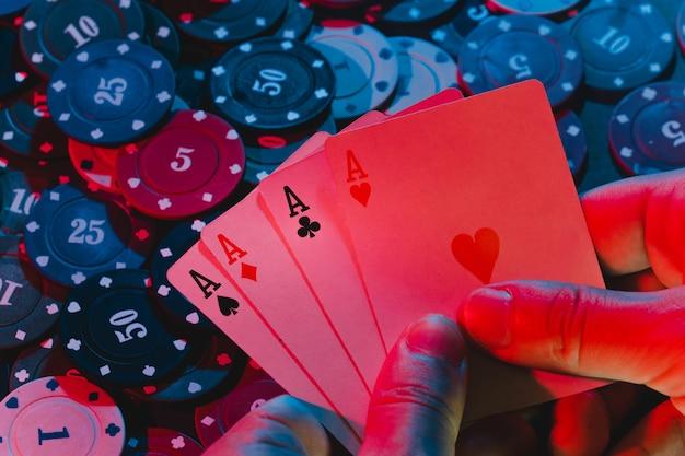 Mannenhanden houden kaarten vast, een set azen op de achtergrond van het spelen van fiches