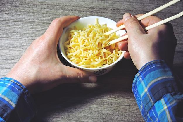 Mannenhanden houden noedels met stokjes. chinese noedels, stokjes, handen.